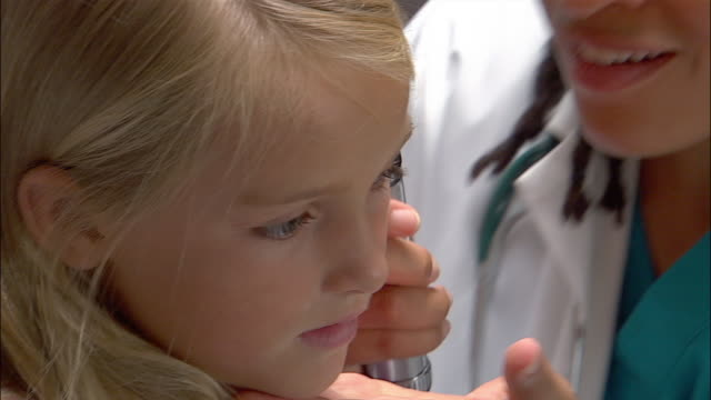 Close up panning doctor examining young girl's ear with otoscope