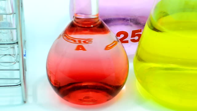 close up panning : much color of chemicals in different glassware