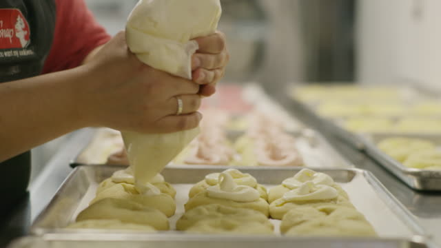 close up panning shot of baker decorating cookies with icing / salt lake city, utah, united states - icing stock videos and b-roll footage