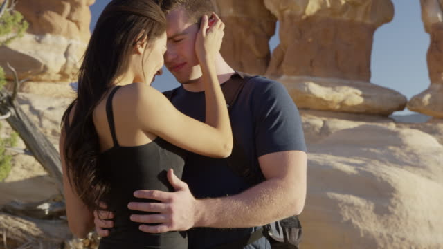 stockvideo's en b-roll-footage met close up panning shot of couple hugging and posing in desert / escalante, utah, united states - handen op de heupen