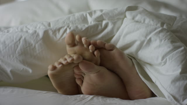 Close up panning shot of cuddling feet of couple in bed / Cedar Hills, Utah, United States