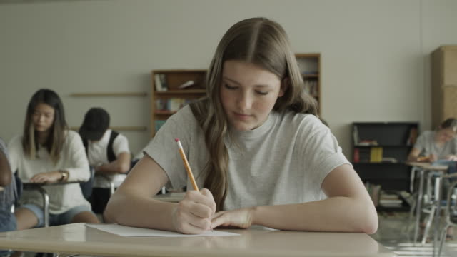 close up panning shot of girl reading then answering test question in school classroom / provo, utah, united states - exam stock videos & royalty-free footage