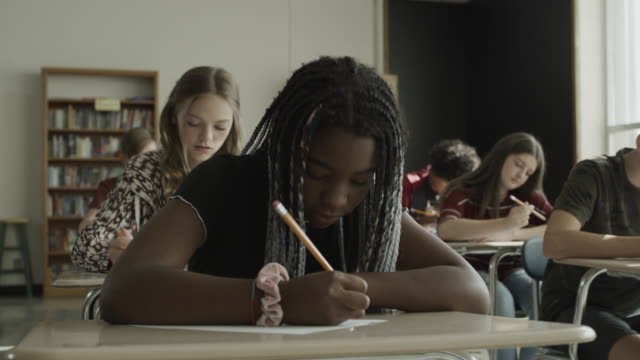close up panning shot of girl waiting then beginning test in school classroom / provo, utah, united states - exam stock videos & royalty-free footage