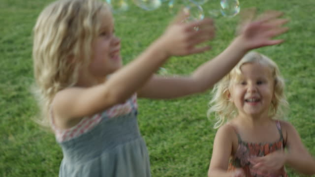 stockvideo's en b-roll-footage met close up panning shot of girls chasing bubbles outdoors / orem, utah, united states - orem utah
