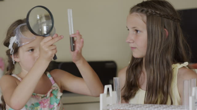 close up panning shot of girls examining test tubes with magnifying glass / orem, utah, united states - orem utah stock videos & royalty-free footage