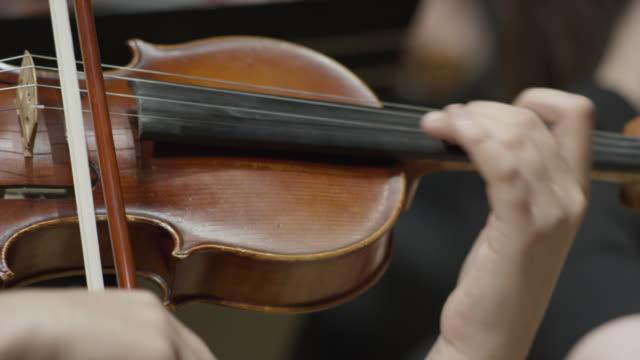 close up panning shot of girls playing violin in orchestra / salt lake city, utah, united states - violin stock videos & royalty-free footage