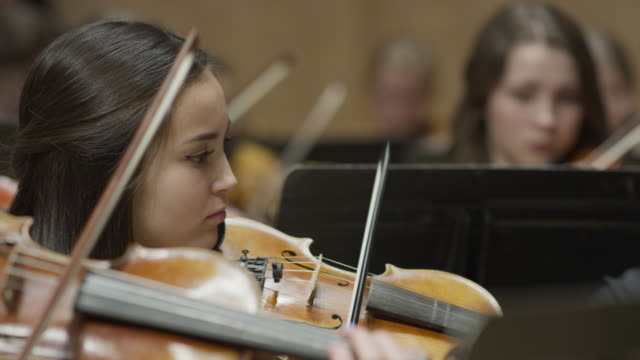 Close up panning shot of girls playing violin in orchestra / Salt Lake City, Utah, United States