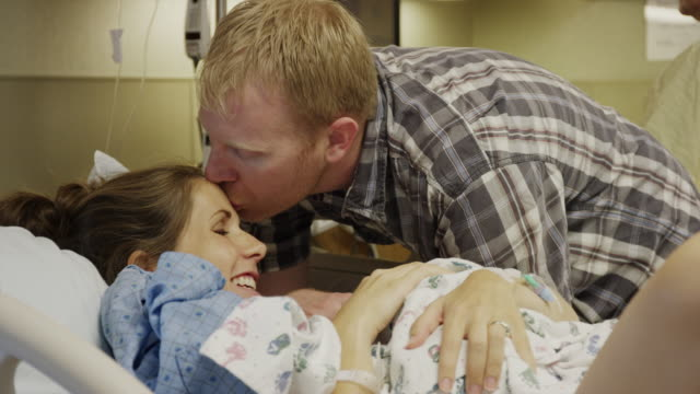 close up panning shot of man kissing forehead of wife after childbirth / midvale, utah, united states - baby blanket stock videos and b-roll footage