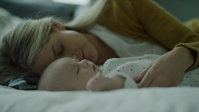 close up panning shot of mother and baby son napping on bed / lehi, utah, united states - lehi stock videos & royalty-free footage