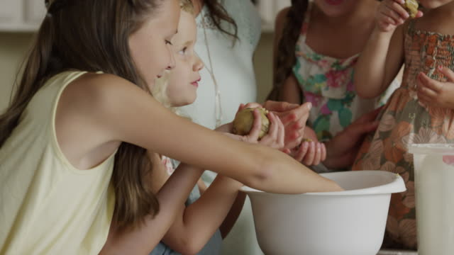 close up panning shot of mother and daughters baking cookies / orem, utah, united states - 子供4人の家庭点の映像素材/bロール