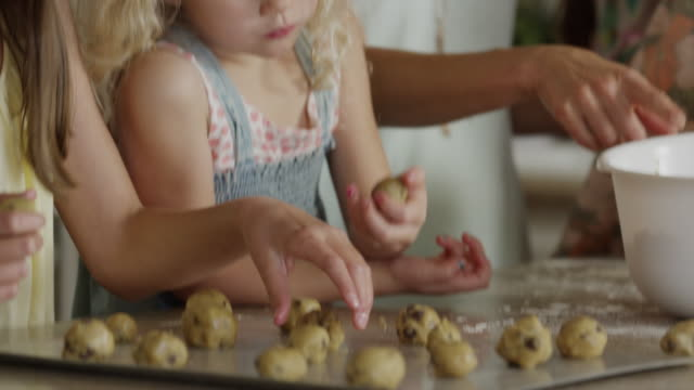 close up panning shot of mother and daughters rolling cookie dough / orem, utah, united states - orem utah stock videos & royalty-free footage