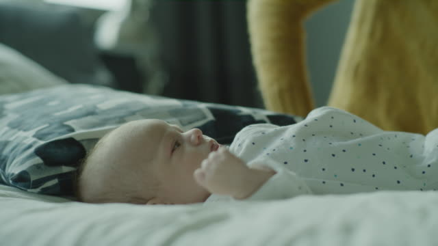 stockvideo's en b-roll-footage met close up panning shot of mother kissing and hugging baby son laying on bed / lehi, utah, united states - driekwartlengte