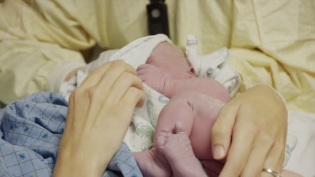 close up panning shot of nurse wiping head of newborn baby / midvale, utah, united states - childbirth stock videos and b-roll footage