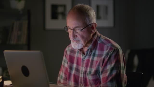vídeos y material grabado en eventos de stock de close up panning shot of older man video chatting on laptop / cedar hills, utah, united states - voz sobre ip