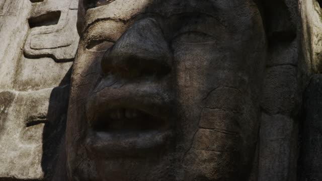close up panning shot of stone face at mask temple / mask temple, lamani, belize,  - figura maschile video stock e b–roll