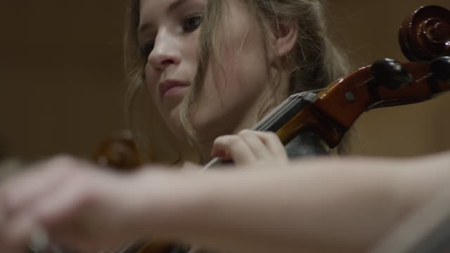 close up panning shot of students playing cellos in orchestra / salt lake city, utah, united states - orchestra stock videos & royalty-free footage
