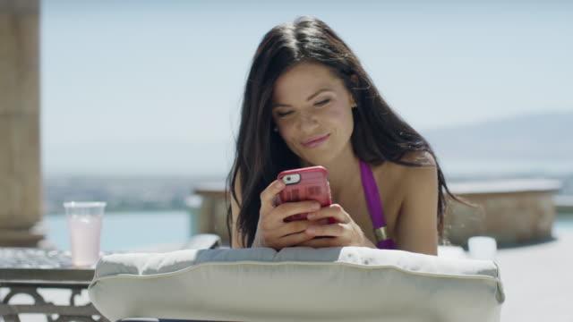 close up panning shot of sunbathing woman texting on cell phone / cedar hills, utah, united states - braunes haar stock-videos und b-roll-filmmaterial