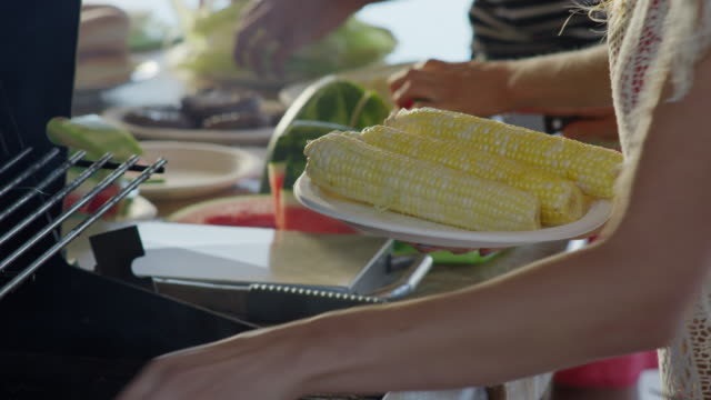 Close up panning shot of woman placing corn on grille for barbecue / Cedar Hills, Utah, United States