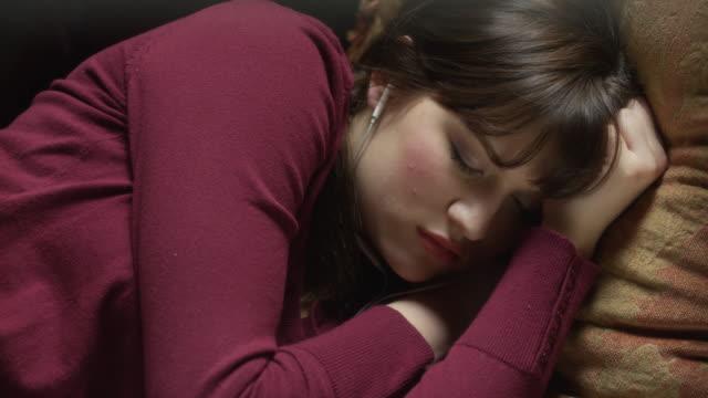 Close up panning shot of woman sleeping on sofa / Cedar Hills, Utah, United States