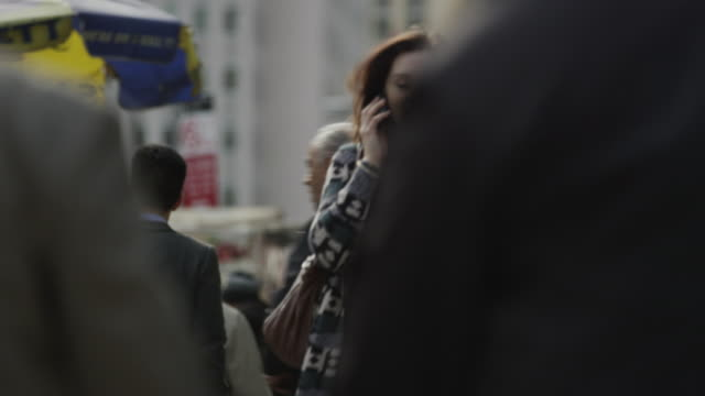 Close up panning shot of woman talking on cell phone in city / New York City, New York, United States