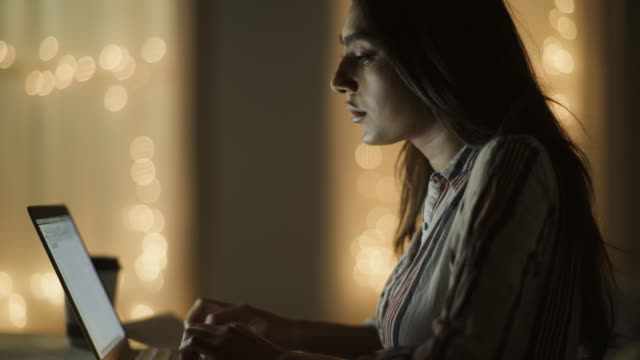 close up panning shot of woman typing on laptop at night / cedar hills, utah, united states - convenience stock videos & royalty-free footage