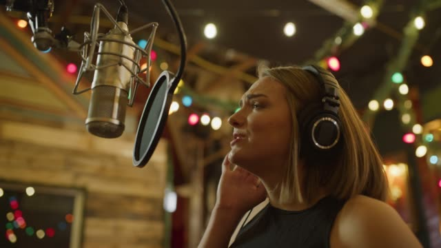 stockvideo's en b-roll-footage met close up panning shot of woman wearing headphones recording vocals with microphone / provo, utah, united states - provo