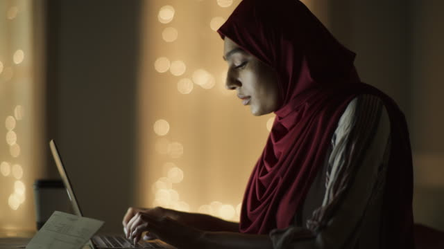 close up panning shot of woman wearing hijab typing on laptop at night / cedar hills, utah, united states - headshot stock videos & royalty-free footage