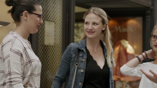 vídeos de stock, filmes e b-roll de close up panning shot of women talking and laughing near store / salzburg, austria - jaqueta jeans
