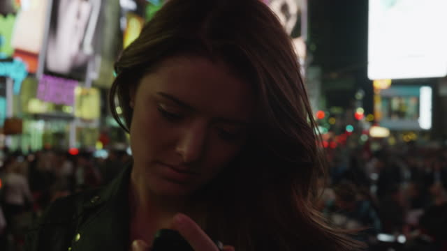 close up panning shot of young woman using camera phone in times square at night / new york city, new york, united states - manhattan theater district stock videos and b-roll footage