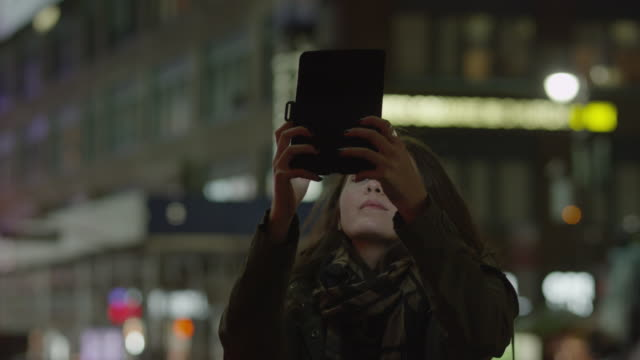 close up panning shot of young woman using digital tablet on urban street at night / new york city, new york, united states - 撮影点の映像素材/bロール