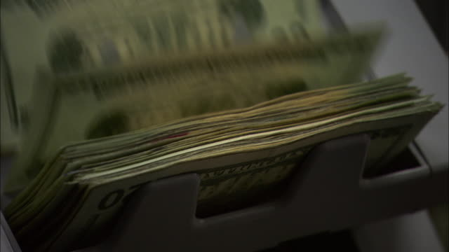 close up pan-right - a cash machine counts twenty-dollar bills. / washington, dc, usa - valuta video stock e b–roll