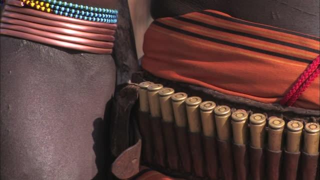 close up pan-right - a native wears an ammunition belt. / ethiopia - kulbälte bildbanksvideor och videomaterial från bakom kulisserna