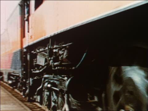 vidéos et rushes de 1954 close up pan passenger train passing people waiting at train station / industrial - 1954