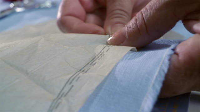 close up pattern being pinned to fabric - cucire video stock e b–roll