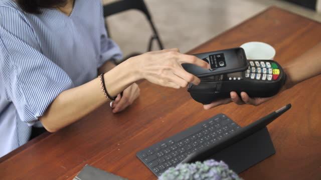 クローズ アップ携帯電話非接触型決済で支払い - 支払い点の映像素材/bロール