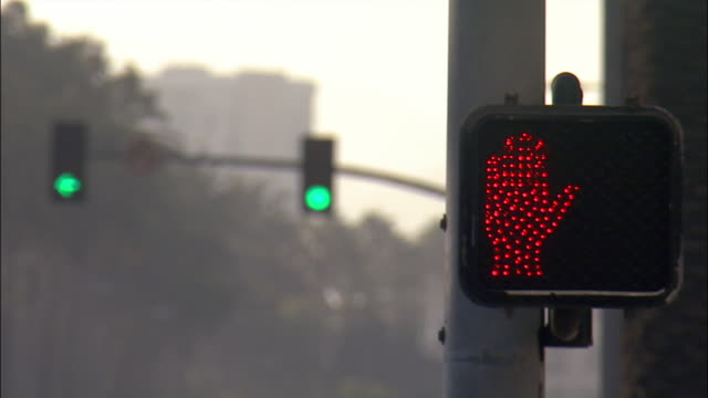 close up pedestrian crossing signal changing from walk to green to red with traffic signal in background / santa monica, los angeles, california - traffic light stock videos & royalty-free footage
