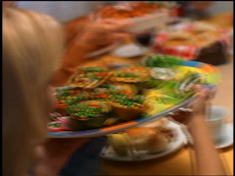 close up pan people passing food at holiday table / boy refusing food from man / thanksgiving - refusing stock videos & royalty-free footage