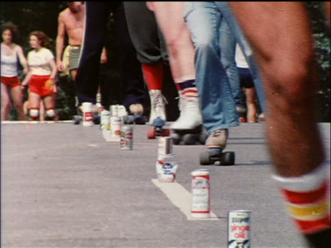 1978 close up people's legs skating roller skating slalom thru line of aluminum cans on ground / nyc - 1978 stock videos & royalty-free footage