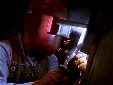 close up person in safety helmet welding indoors - welding helmet stock videos & royalty-free footage