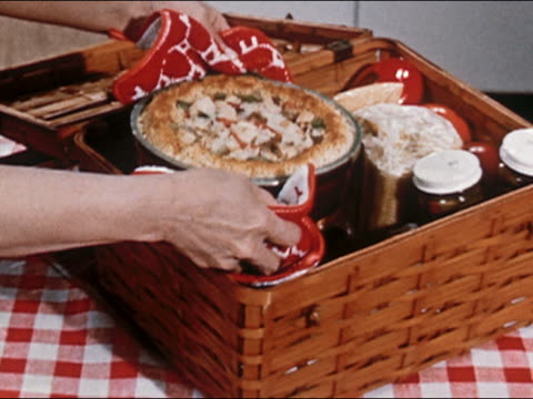 vidéos et rushes de 1951 close up person placing baked turkey casserole in picnic basket with other food and supplies / audio - panier de pique nique