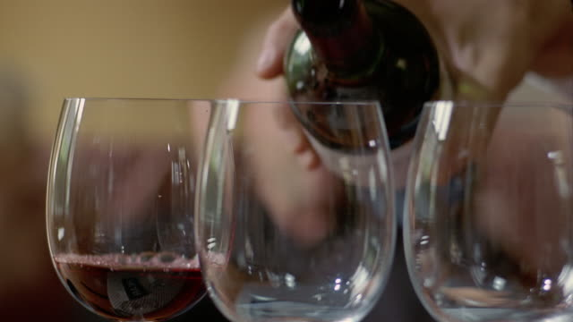 Close up person pouring red wine into wine glasses