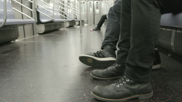 Close up, person taps feet on subway
