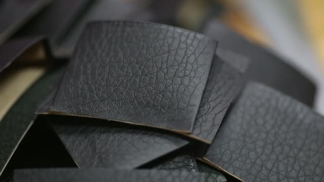 vídeos y material grabado en eventos de stock de close up, pieces of leather are folded together by a worker manufacturing wallets at a leather workshop in the dharavi area of mumbai, india, on... - iva