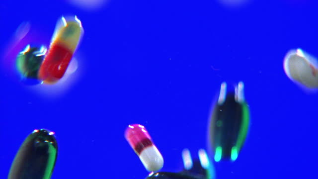 close up pills falling with blue background - pill addiction stock videos & royalty-free footage