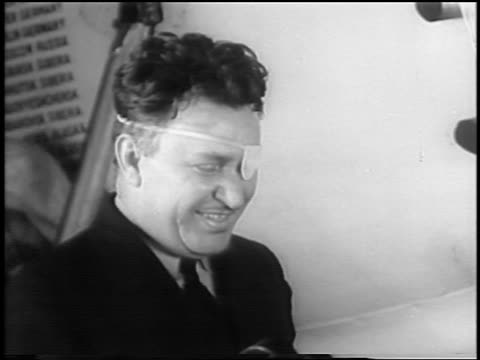 vidéos et rushes de b/w 1935 close up pilot wiley post with eye patch talking / newsreel - 1935