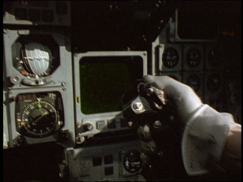 close up pilot's hand operating joystick in cockpit of MRCA Tornado fighter jet / gauges in background