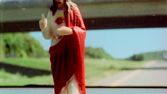vidéos et rushes de close up plastic jesus on car dashboard with road and changing landscape in background / pennsylvania - procédé croisé