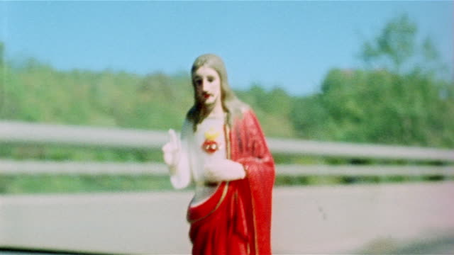 Close up plastic Jesus on car dashboard with road and changing landscape in background / Pennsylvania