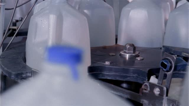 Close up plastic jugs of water rotating on conveyor belt at water purification plant / San Antonio, Texas