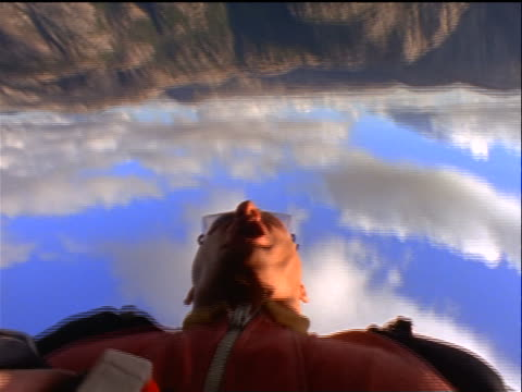 vídeos de stock, filmes e b-roll de close up point of view face of male base jumper falling past cliff + shouting / parachute opening above him / sweden - paraquedismo